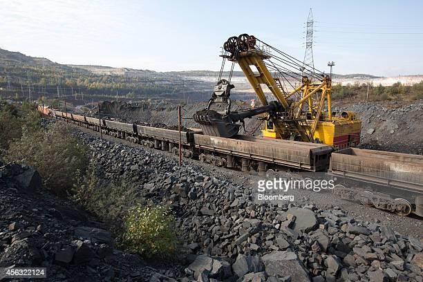 An excavator loads cargo wagons on a freight train with iron ore from the Stoilensky GOK iron ore mine and processing plant operated by OAO...