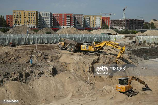 An excavator loads dirt onto a dump truck in the pit of the Quartier Heidestrasse residential apartment complex construction site part of the...