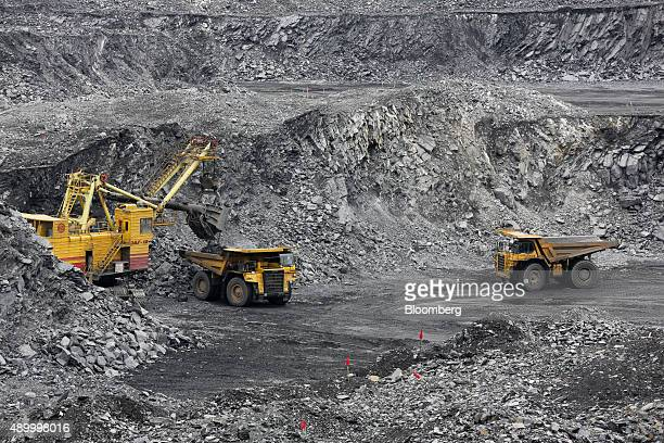 An excavator machine loads a Komatsu Ltd truck with rock ore in the open pit at the Verninsky GOK gold mine and processing plant operated by Polyus...