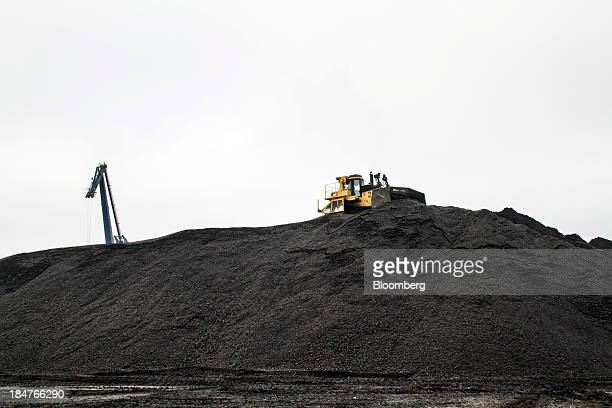 An excavator moves coal used to fuel Dong Energy's Avedore 1 a coalfired CHP power plant at the company's Avedoerevaerket site in Hvidore Denmark on...