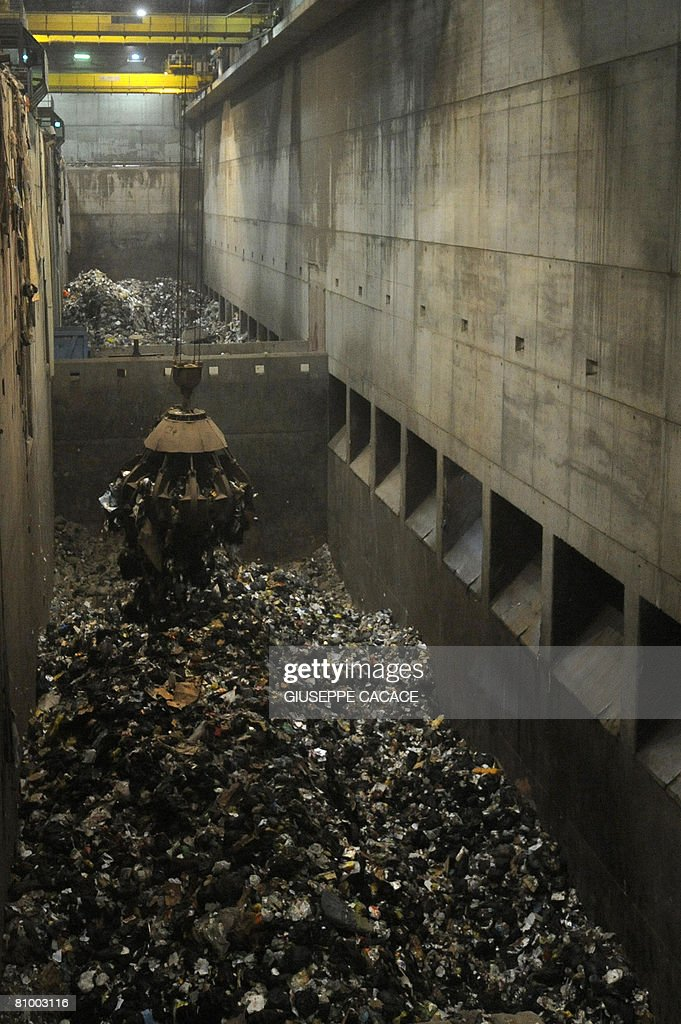 An excavator moves rubbish inside the Si : News Photo