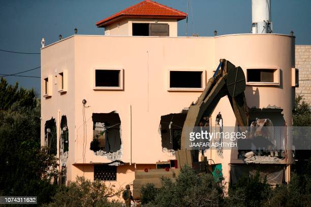 An excavator of the Israeli forces destroys the flat of Palestinian man Ashraf Naalwa in the village of Shuwaykah near the West Bank city of Tulkarem...