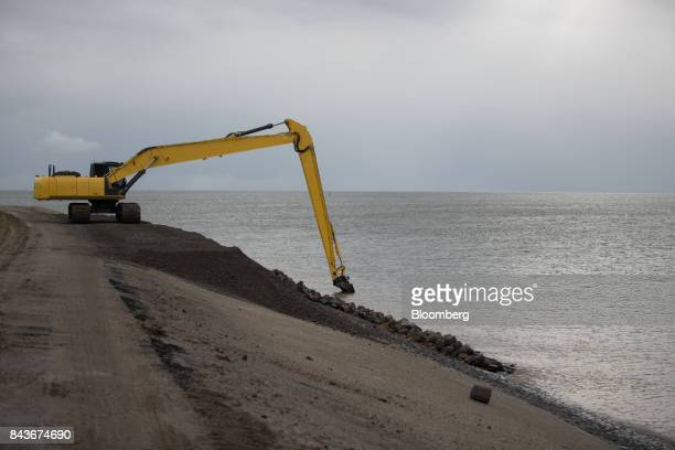 An excavator operates during dike renovation work being carried out by Arcadis NV on the Wadden Sea coastline on Texel island in Oudeschild...