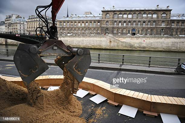 An excavator puts down sand on July 18 2011 in Paris along the Seine River in preparation of the 10th edition of Paris Plages an ephemeral beach...