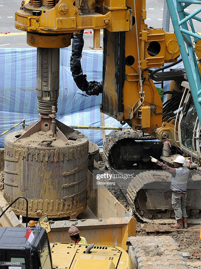 An excavator removes earth at a construction site for a SMRT Corp tunnel in Singapore, on Sunday, Dec. 30, 2012. Singapore may grapple with elevated inflationary pressures for a third year in 2013, reducing scope for the central bank to provide stimulus to an economy that probably entered a technical recession this quarter. Photographer: Munshi Ahmed/Bloomberg via Getty Images