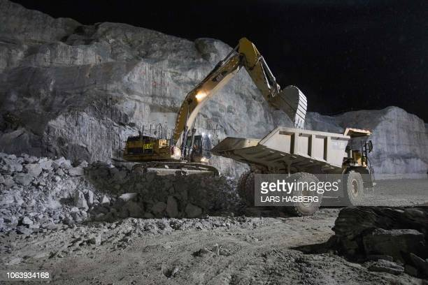 An Excavator removes rocks onto an articulated dump truck at HydroQuebec's Romaine 4 hydroelectric dam in the CôteNord Administrative Region of...