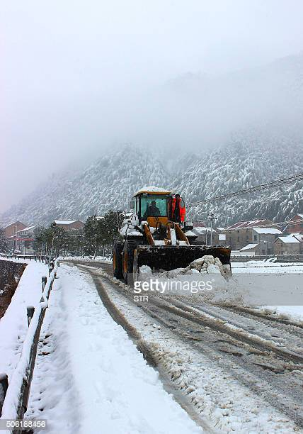 An excavator removes snow on a highway in Tonglu county in Hangzhou east China's Zhejiang province on January 22 2016 Schools have been suspended and...