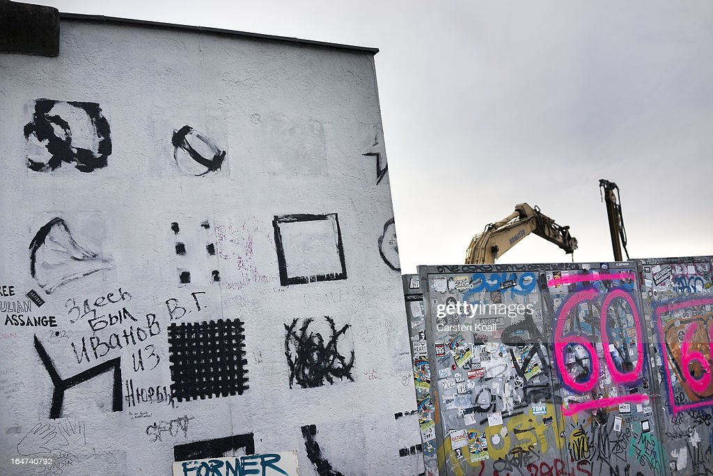 An excavator rises up after a section of the Berlin Wall was removed to make way for a luxury apartments development on March 27, 2013 in Berlin, Germany. Activists were seeking to stop a stretch of the Berlin Wall, known as the East Side Gallery, from being developed on by a real estate development company. A previous attempt by the developer to remove approximately 25 meters of the wall sparked protests that led to minor clashes with police. Negotiations had been underway and city officials had even offered the developer an alternative property, though removal continued today unannounced and to the surprise of opponents. The East Side Gallery is over one kilometer long and is among the city's biggest tourist attractions.