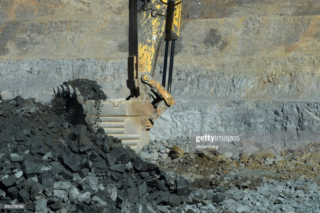 An excavator scoops up ore in the White Foil open mine pit at Evolution Mining Ltd.'s gold operations in Mungari, Australia, on Tuesday, Aug. 8, 2017. Evolution Mining is Australias second-largest gold producer. Photographer: Carla Gottgens/Bloomberg via Getty Images