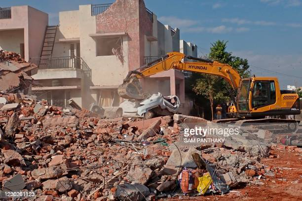An excavator works amid the debris of two residential bungalows that collapsed after a gaseous blast at Kalol town in Gandhinagar on December 22,...