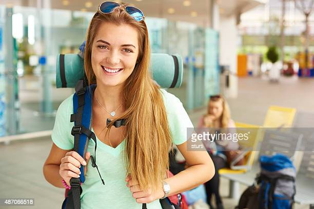 An excited backpacker smiles to camera
