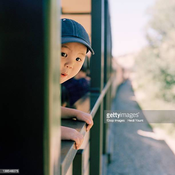 An excited boy leaning out of a train window