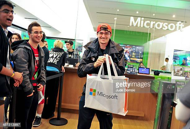 An excited fan shows of his new Xbox One after purchasing it at midnight from the Microsoft retail store at the Burlington Mall on November 21 2013...