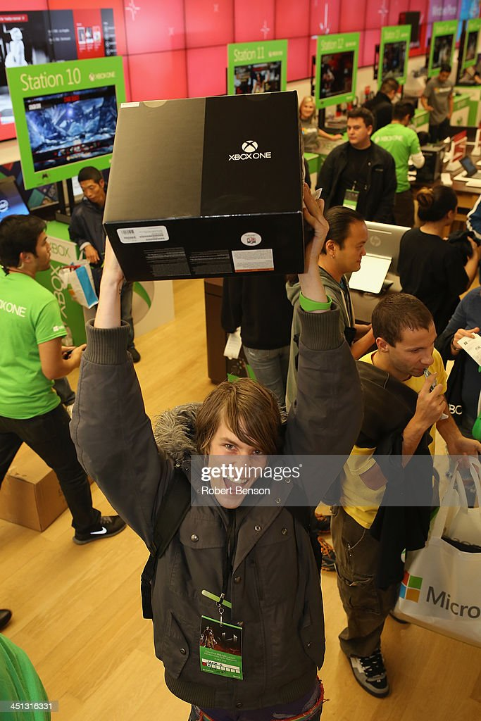 An excited fan shows off his new Xbox One after purchasing it at