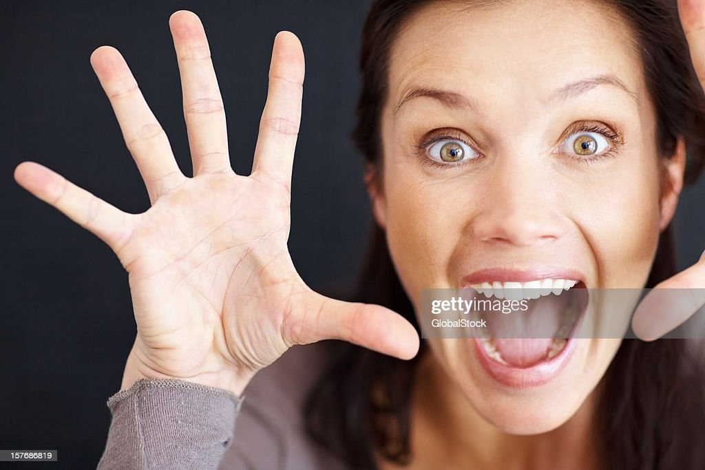 An excited middle aged woman screaming against black background : Stock Photo
