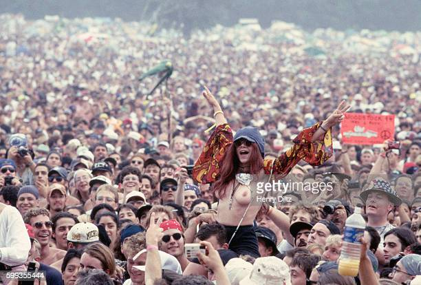 An excited young woman bares her breasts in a huge crowd at Woodstock '94 a threeday rock music festival in Saugerties New York