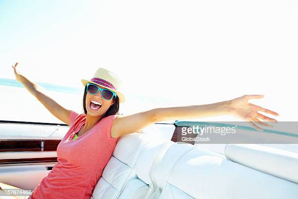 An excited young woman sitting in car on beach