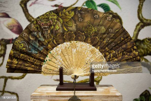An exclusively produced hand fan with sticks and handles made from cow bone and decorated with Barong painted and carved by Balinese artist is...
