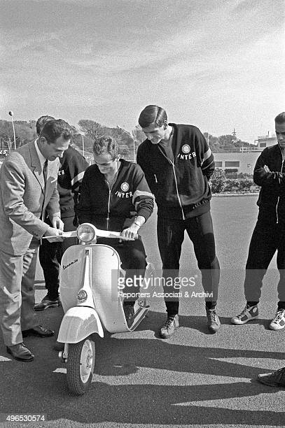 An executive of Piaggio delivering a Vespa as a gift to the players of Italian football club Inter One of the players getting on the seat to try it...