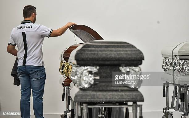 An executive of the Brazilian football team Chapecoense Real looks inside a coffin of one of the players killed in the plane crash in the Colombian...