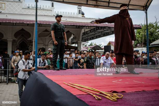 An executor known as 'algojo' caning a man in public for spending time with a woman who is not her wife which is violations against Sharia law on...