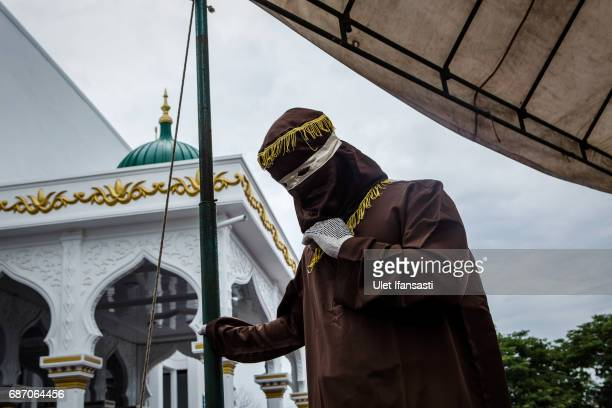 An executor known as 'algojo' stands as prepare public caning for violations against Sharia law at Syuhada mosque on May 23 2017 in Banda Aceh...