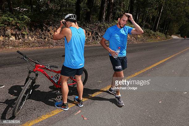 An exhausted Dale Thomas reacts handing his bike to a teamate at the half way chage over up Mount Buller during the Carlton Blues AFL training camp...