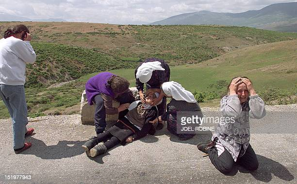 An exhausted ethnic Albanian refugee from Kosovo who collapsed moments after having crossed into Albania 08 May 1999 is helped by family members as...