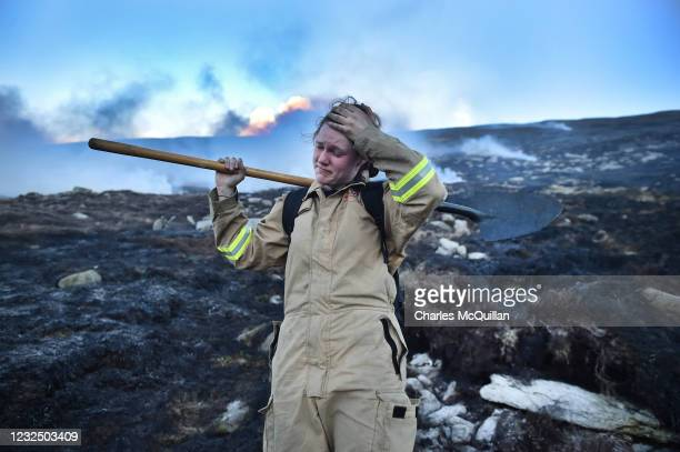 An exhausted Haley Agnew wipes sweat from her brow as she works with fellow firefighters on Slieve Donard mountain on April 24, 2021 in Newcastle,...