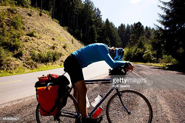 An exhausted male cyclist leans over his touring bike while climbing Mattole Road near Ferndale, California.
