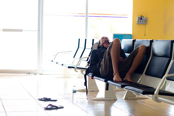 An exhausted male traveler waits in an airport terminal for his flight to arrive at the Manzanillo International Airport in Colima, Mexico.