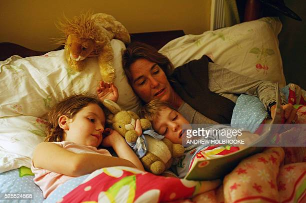 An exhausted mother reads to her children at bedtime.