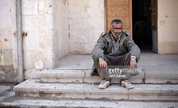 An exhausted resident of Sarmin takes a break from clearing rubble from his property after tanks attacked the town on April 9 2012 in Syria...