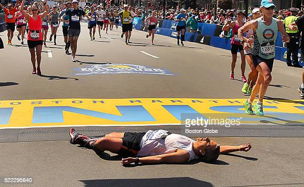 An exhausted runner falls to the ground after crossing the finish line of the 120th Boston Marathon on Monday April 18 2016