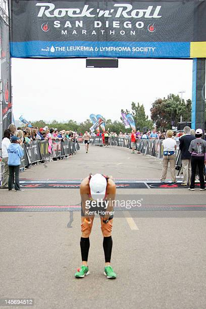An exhausted runner pauses after crossing the finish line at the Rock 'n' Roll Half Marathon on June 3 2012 in San Diego California