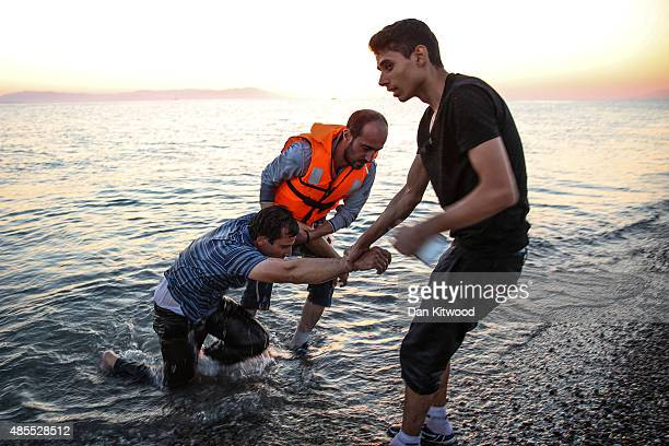An exhausted Syrian man is dragged out of the water after swimming the last 50 metres to shore as migrant families from Syria arrive in an inflatable...