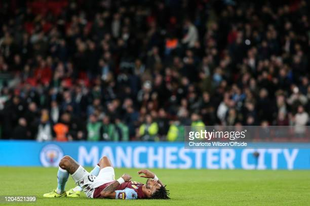 An exhausted Tyrone Mings of Villa collapses after the final whistle as Manchester City flashes up on the advertising boards after the Carabao Cup...