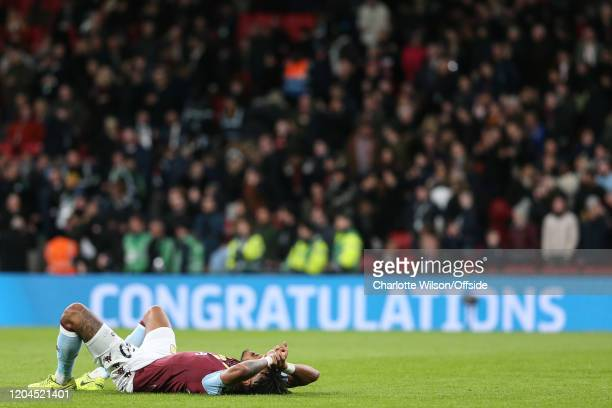 An exhausted Tyrone Mings of Villa collapses after the final whistle as Congratulations flashes up on the advertising boards after the Carabao Cup...