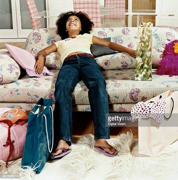 an exhausted young girl sitting on a sofa, surrounded by expensive shopping bags - girl wear jeans and flip flops stock photos and pictures