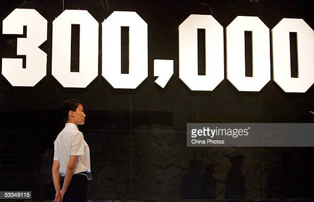 An exhibition worker stands before the number of Nanjing Massacre victims at the National Museum August 10 2005 in Beijing China The 20day exhibition...