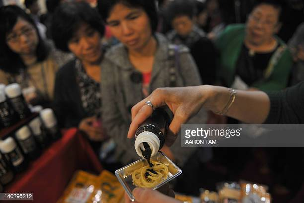 An exhibitioner pours soy sauce on a sampler of ramen at the Japanese Food Exhibition in Hong Kong on March 2 2012 More than 40 companies are touting...