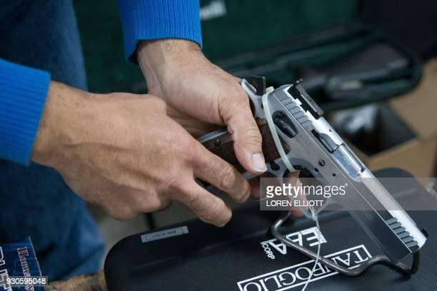 An exhibitor adjusts a handgun during the Sweetwater Rifle and Pistol Club show at Nolan County Coliseum on March 11 2018 in Sweetwater Texas / AFP...