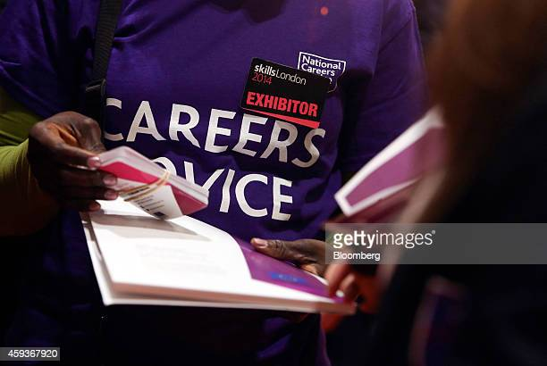 An exhibitor at the National Careers Service job exhibition booth hands an information pack to a visitor during the Skills London job fair in London...