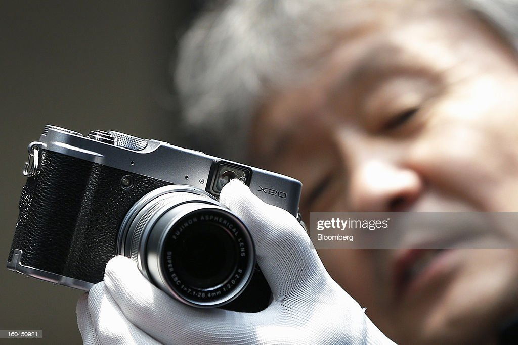 An exhibitor demonstrates a Fujifilm Holdings Corp. X20 digital camera at the CP+ Camera and Photo Imaging Show in Yokohama City, Japan, on Thursday, Jan. 31, 2013. The CP+ Camera and Photo Imaging Show runs from Jan. 31 to Feb. 3. Photographer: Kiyoshi Ota/Bloomberg via Getty Images
