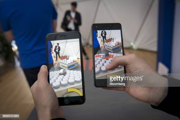An exhibitor demonstrates a multiplayer augmented reality game using a shared cloud space that can be played between both Apple Inc iPhones operating...