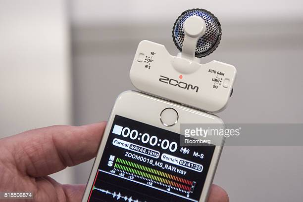 An exhibitor demonstrates a Zoom Corp iQ5 midside stereo microphone attached to an Apple Inc iPhone during the South By Southwest Interactive...