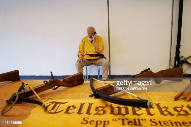 An exhibitor dressed as legendary Swiss hero William Tell speaks on a mobile phone as he sits behind a stall displaying a crossbow during the 45th...