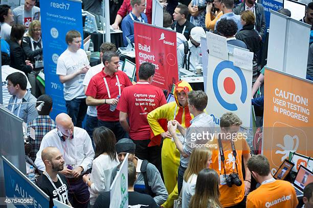 An exhibitor dressed in a chicken costume promotes his business startup company in the main hall titled 'Startup Alley' at the Disrupt Europe 2014...