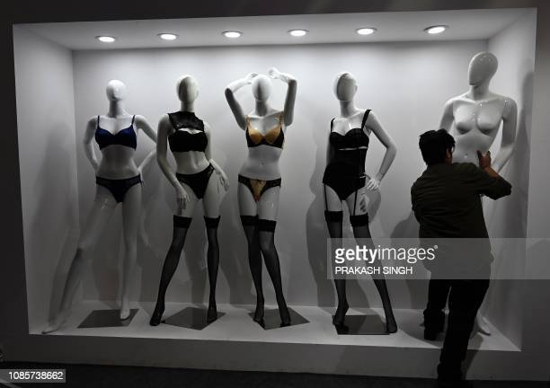 An exhibitor dresses mannequins during Intimasia Expo2019 an Intimate Wear Show in New Delhi on January 21 2019 Retailers from 84 neighboring cities...