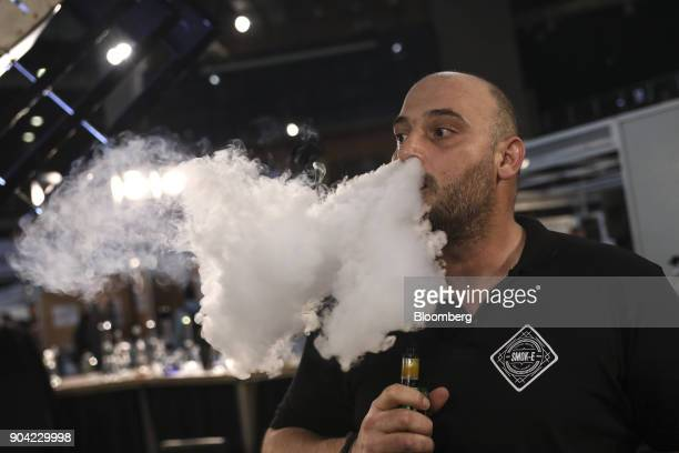 An exhibitor exhales vapor while testing an electronic ecigarette device at the 1st International Cannabis Expo at the Faliro Sports Pavilion in...
